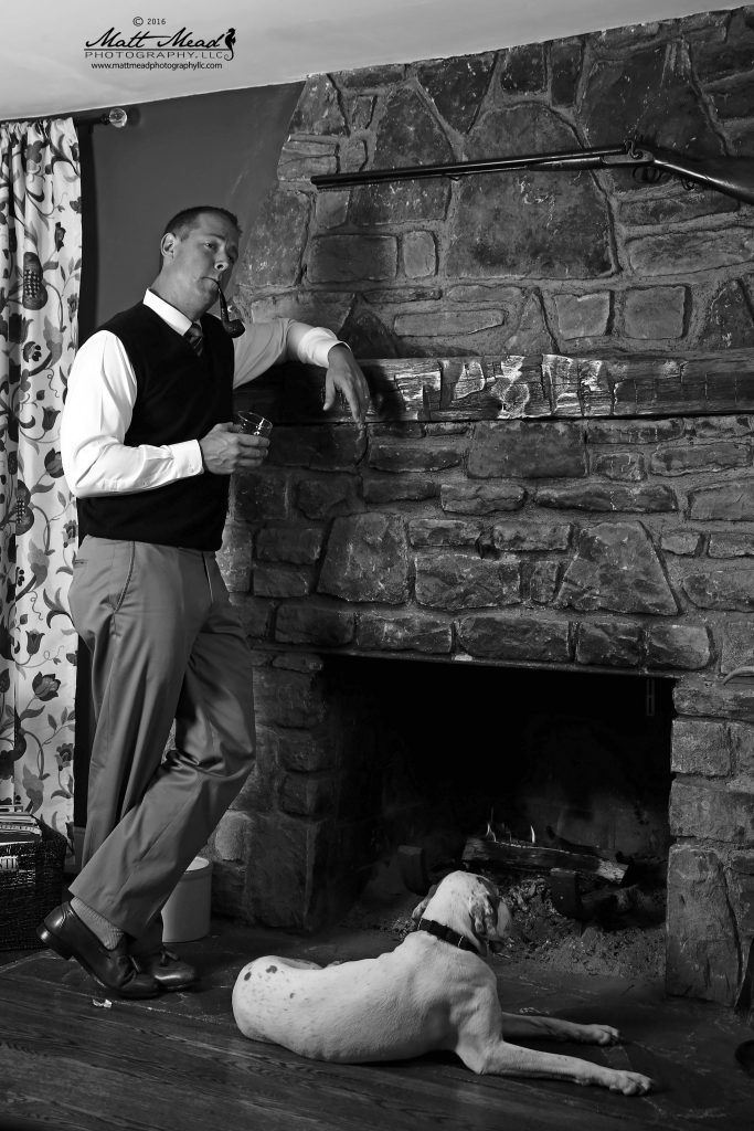 man stands pensively at fireplace in his home with dog laying at his feet in Ligonier, PA