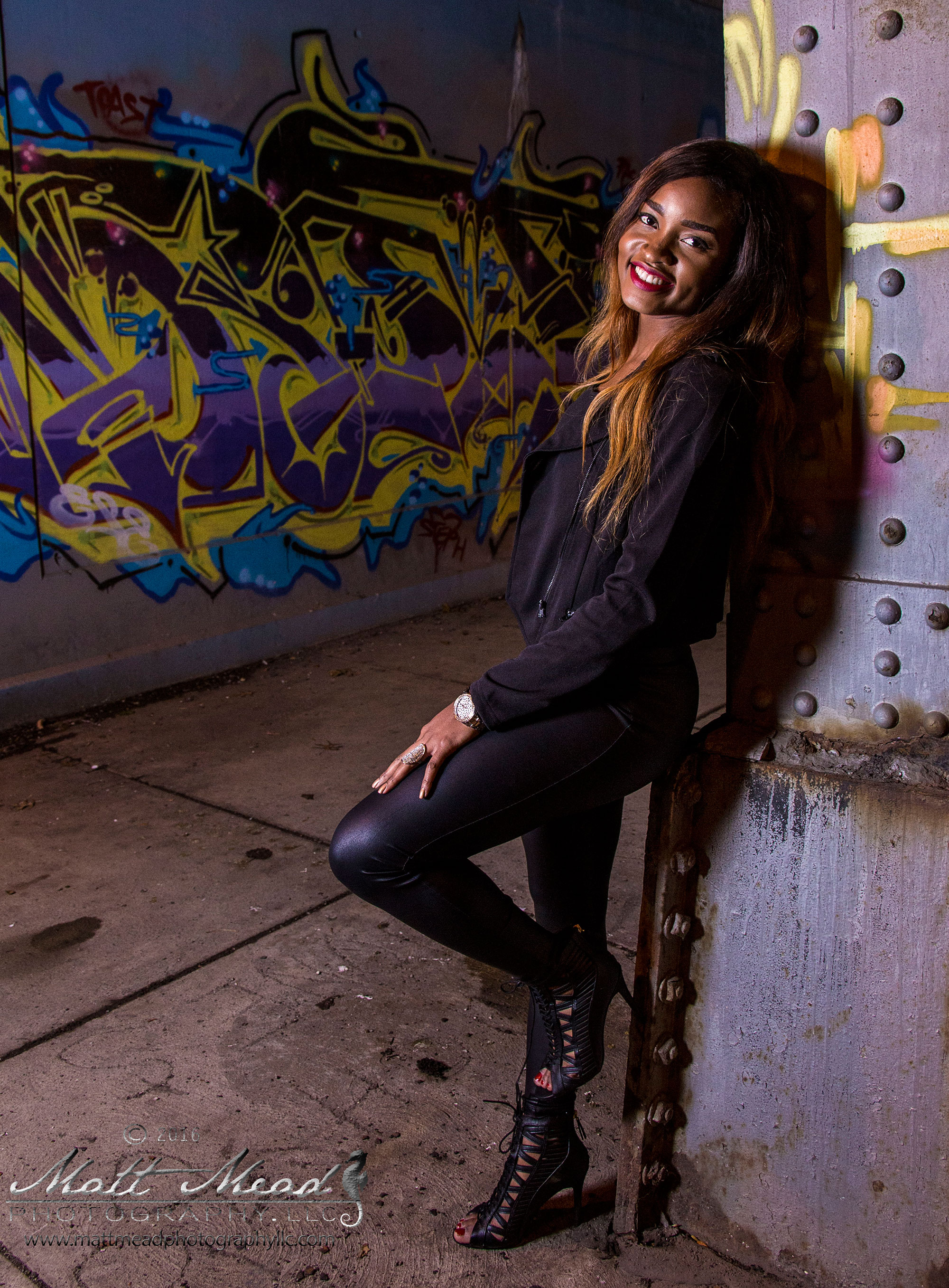 woman smiles at camera with graffiti in background during Erie PA portrait session