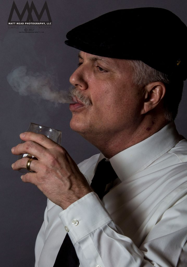 From Erie PA headshot session, portrait of man exhaling cigar smoke getting ready to take a drink from a glass