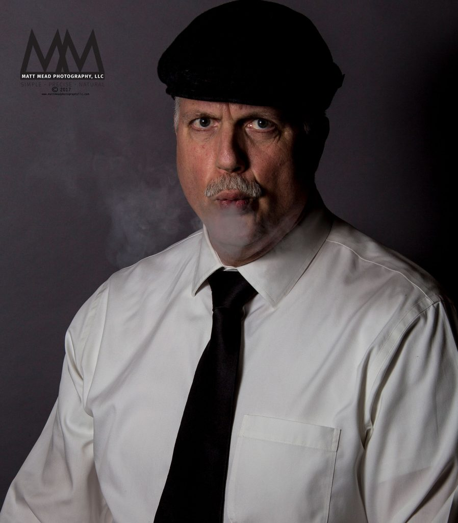 portrait of man exhaling cigar smoke in Erie PA headshot session