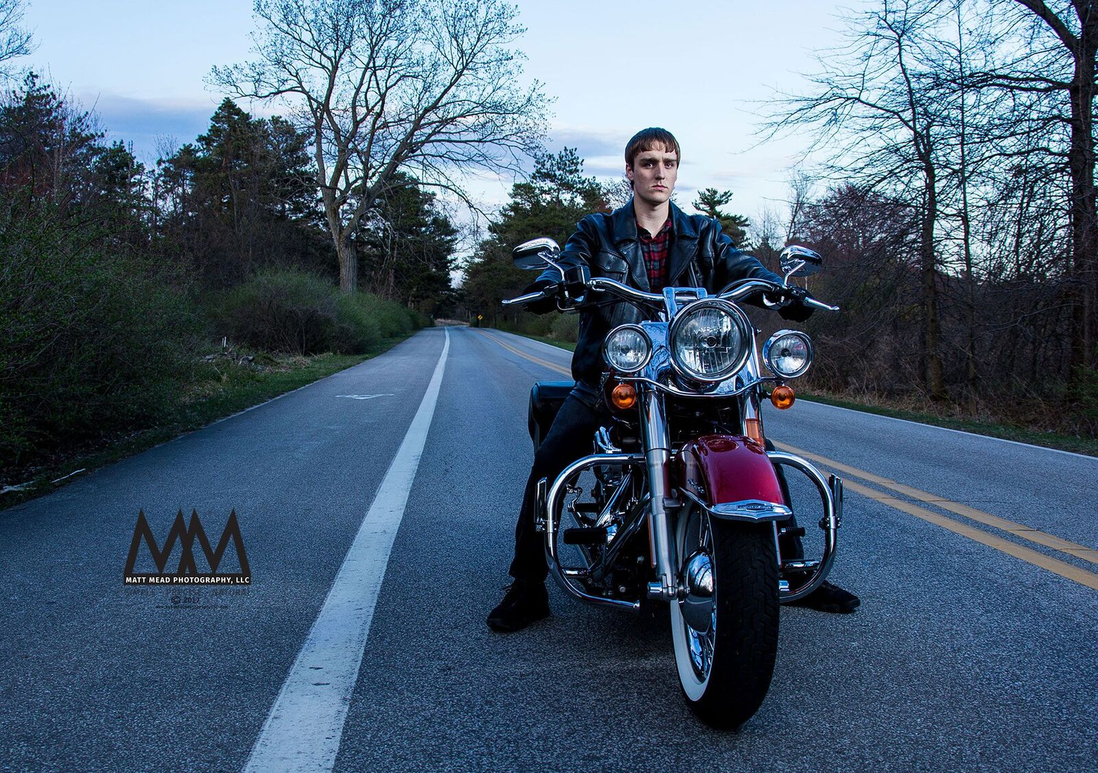 teen driving down the road on motorcycle for Erie PA senior portrait session at Presque Isle state Park