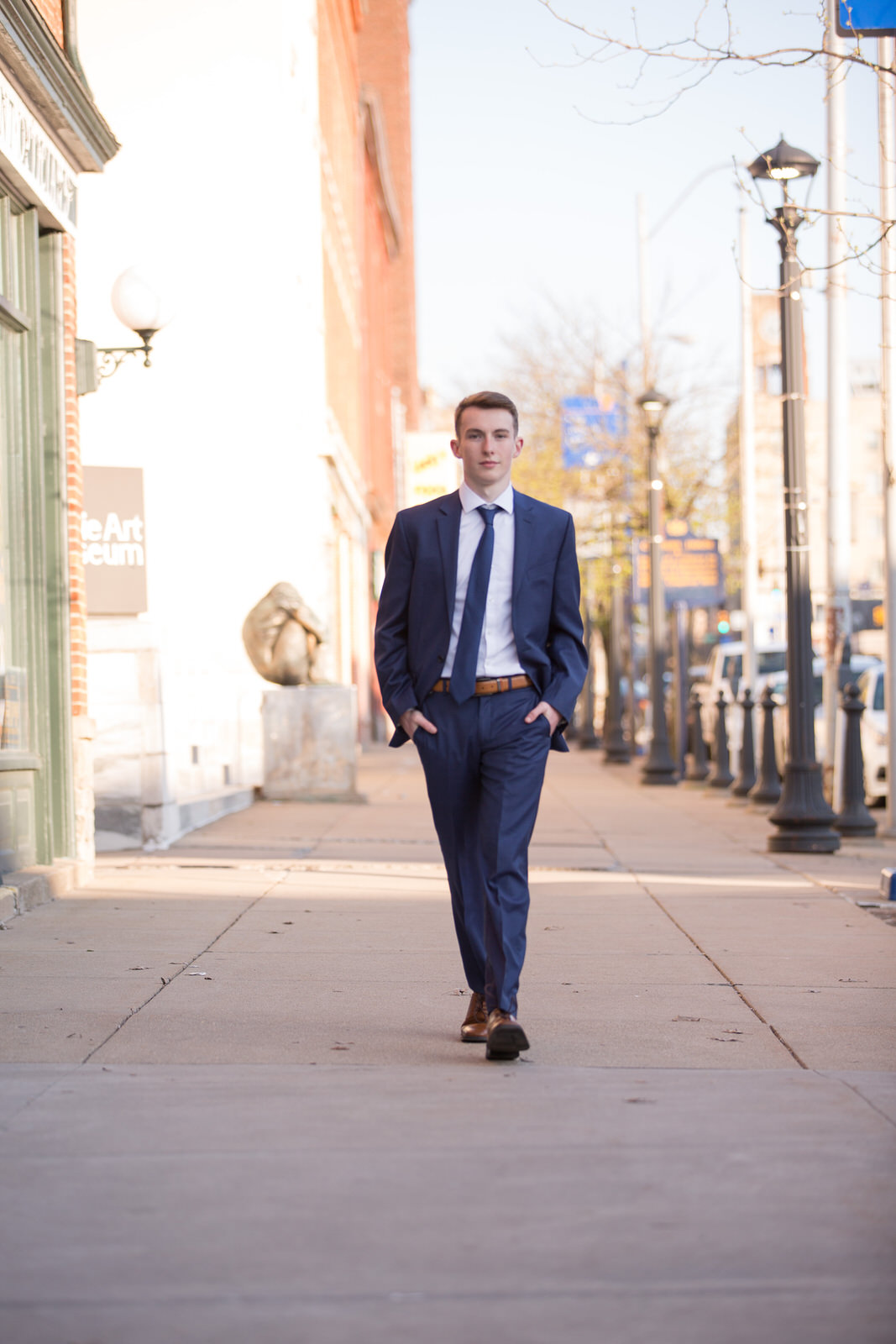 Boy in suit walks down the street for senior portraits in Erie, PA