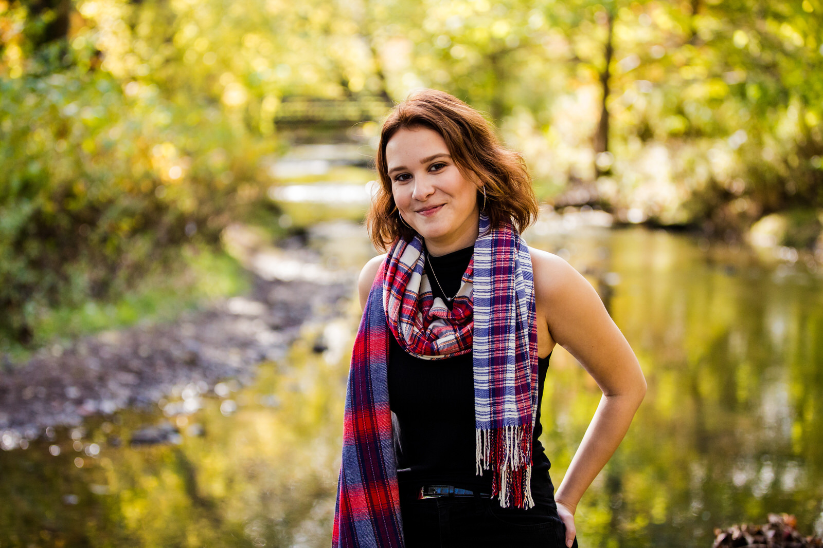 Girls wearing a plaid scarf stands next to a creek in Frontier Park senior portraits in Erie PA