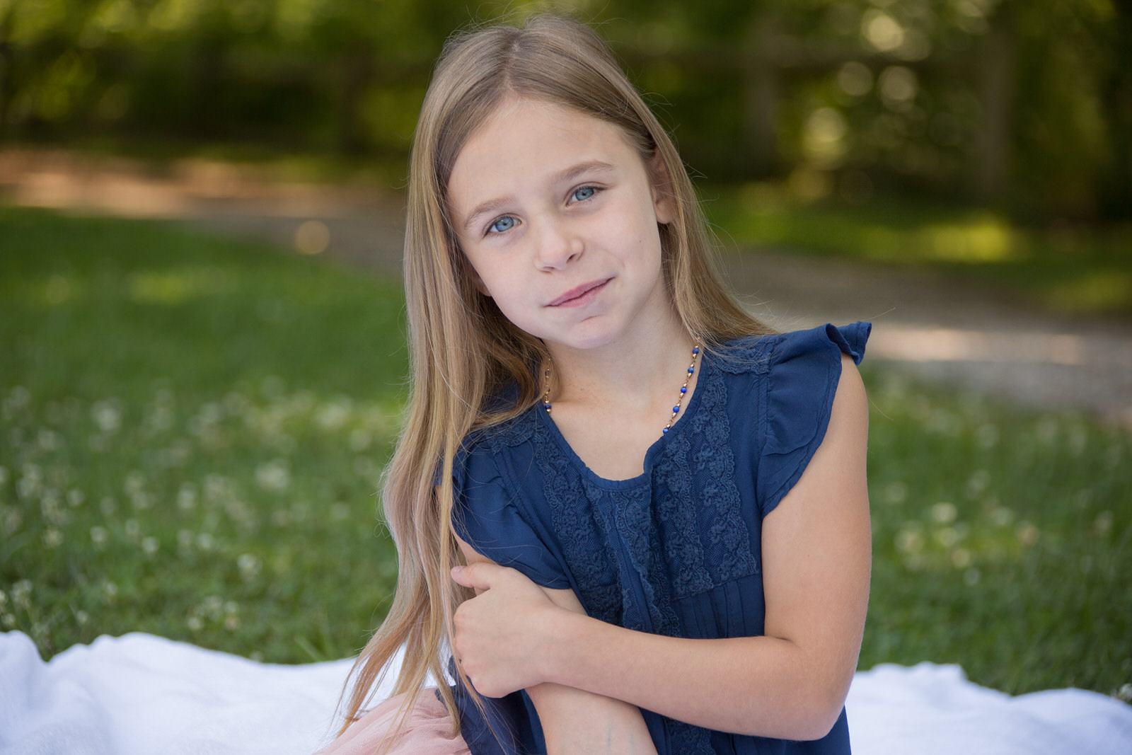 Girl sits on a blanket in a park for family portraits in Erie, PA