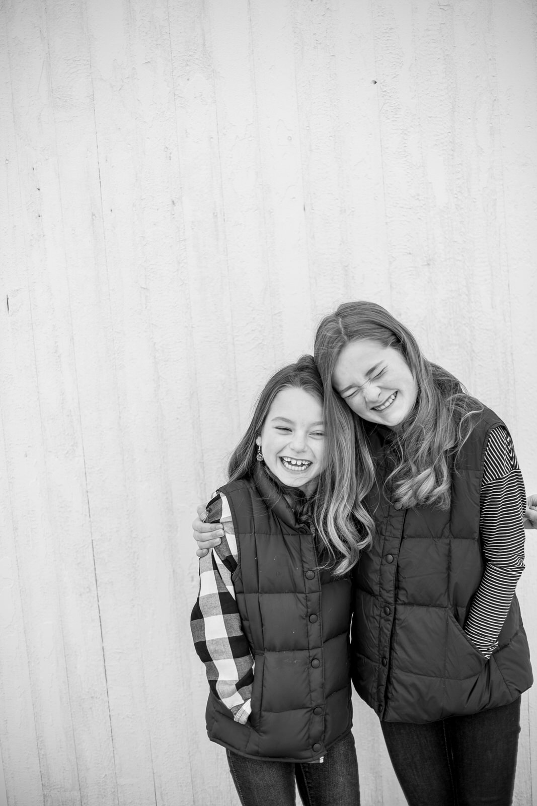 Sisters snuggle together and laugh during family portraits in Ligonier, PA