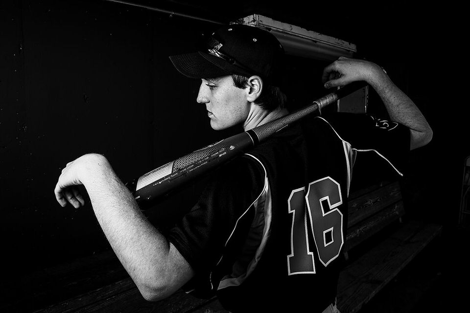 Erie,PA Senior portrait of young man wearing baseball uniform and balancing a bat across his shoulders