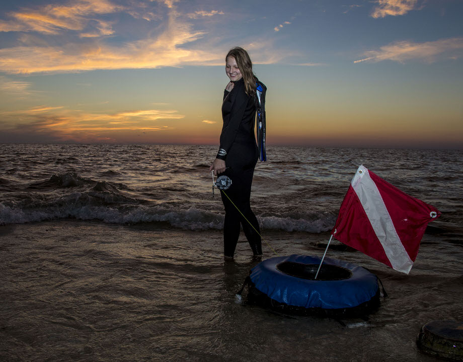 senior portrait of a girl wearing SCUBA gear getting ready to walk into Lake Erie