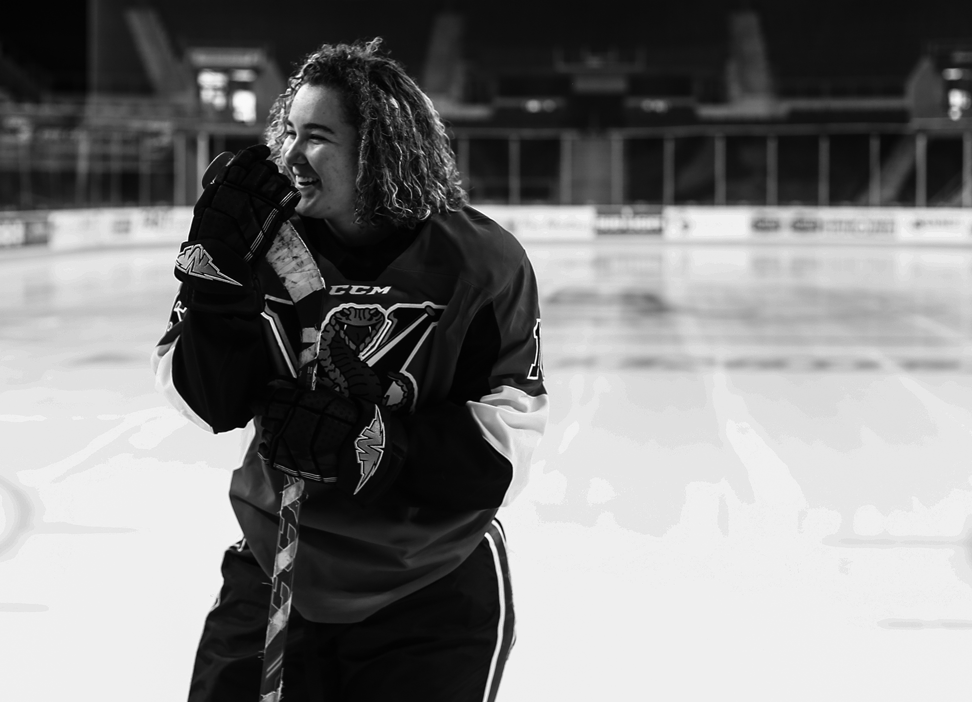Girl laughs during hockey themed Erie senior portraits