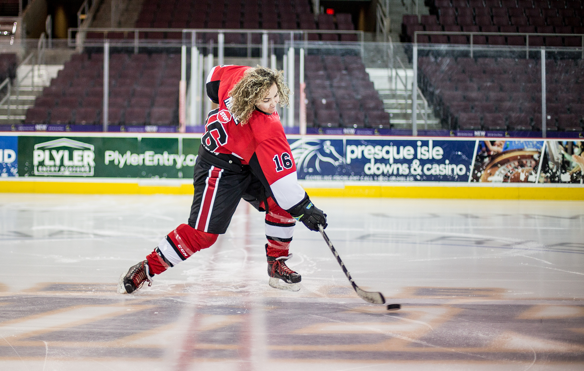 Girl hits a hockey puck toward goal net during Erie senior portraits session