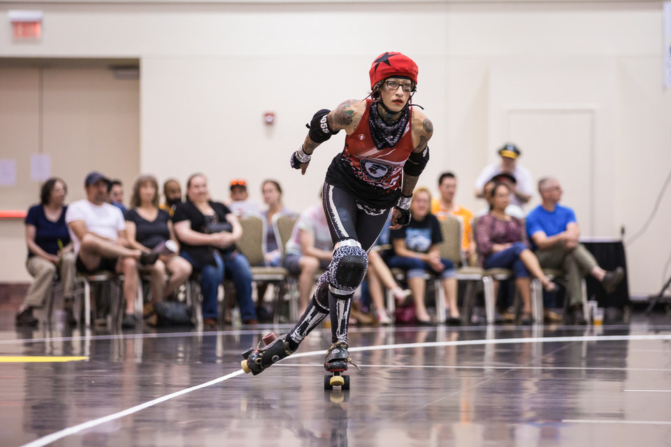Eerie Roller Girls' player skating around the track