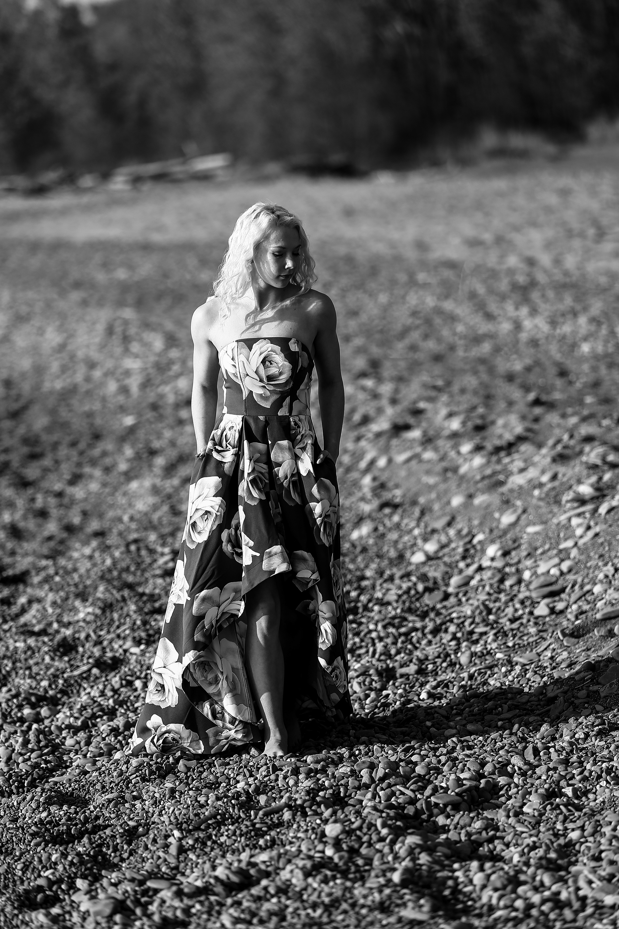 Girl in floral print dress standing on the beach for Sweet Sixteen photos at Presque Isle State Park