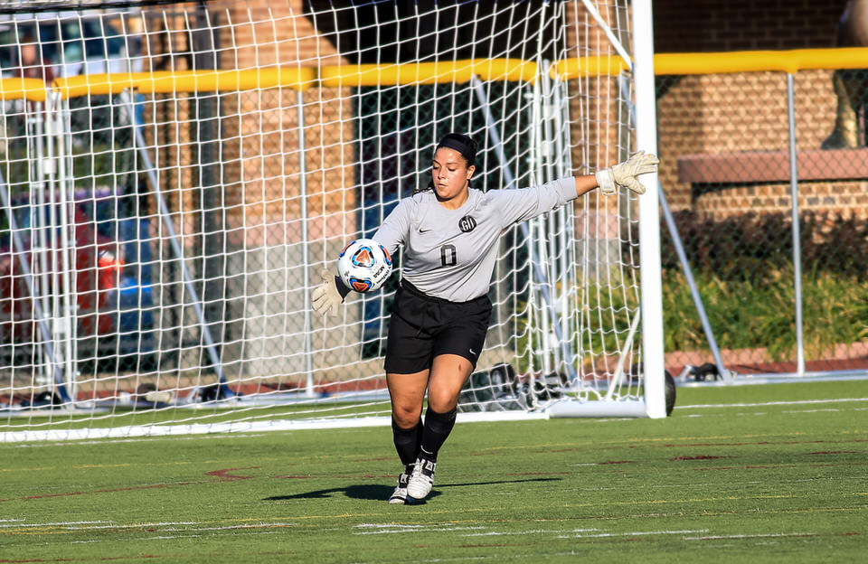 Goalie for Gannon University's women's soccer team kicking ball