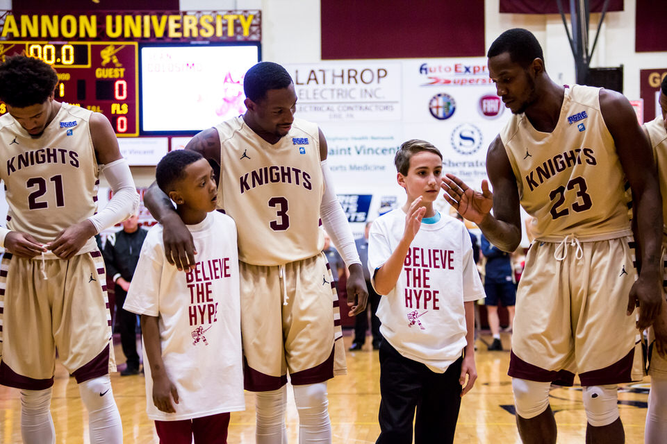 Gannon University's men's basketball players high five Make-A-Wish award recipients