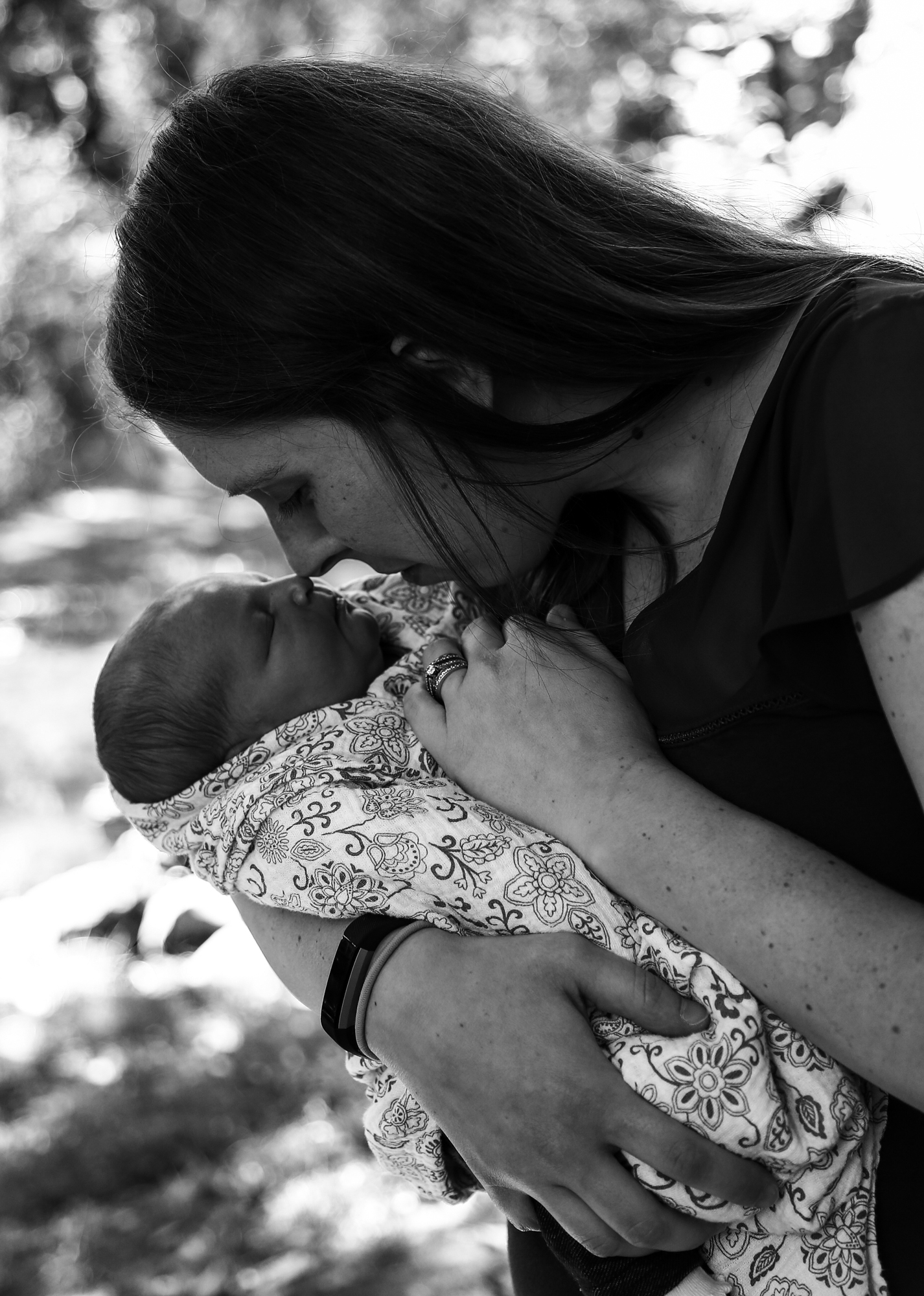 Mother and new baby touching noses for family photos at Frontier Park