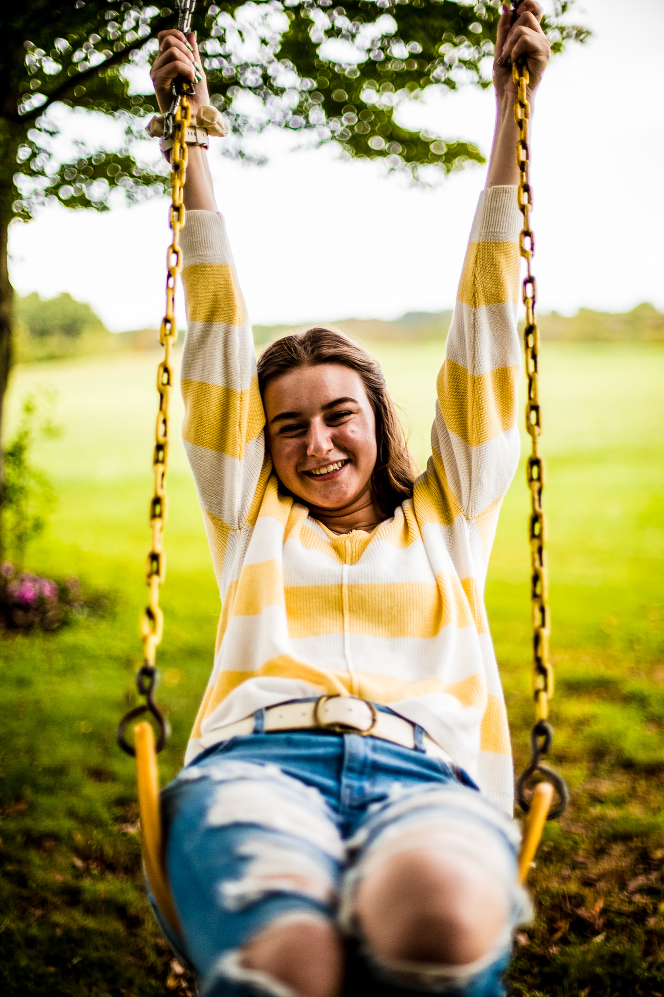 Laughing girl swinging on a swing at her family's farm in Union City, PA