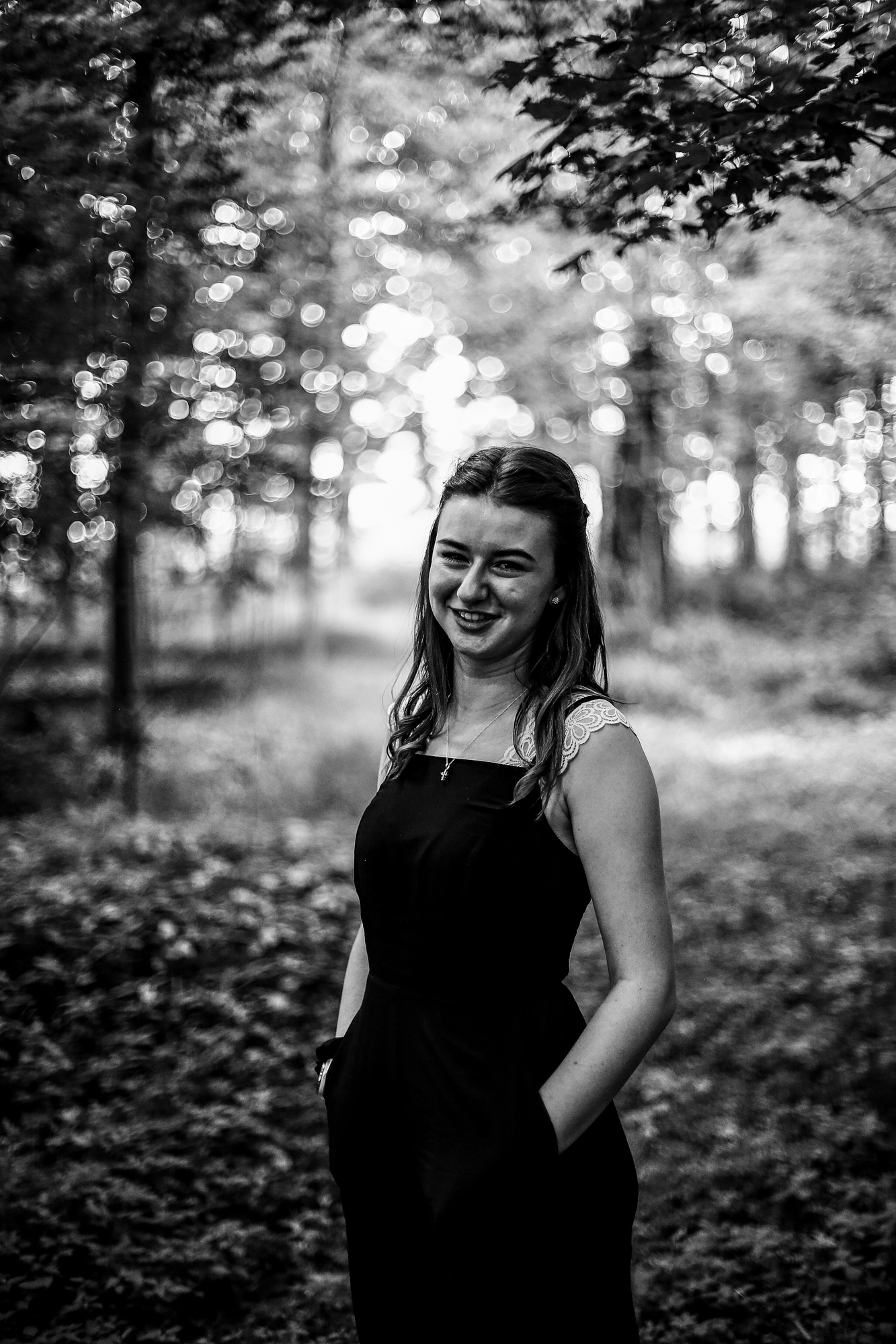 Girl stands in woods next to family farm for rustic senior portraits