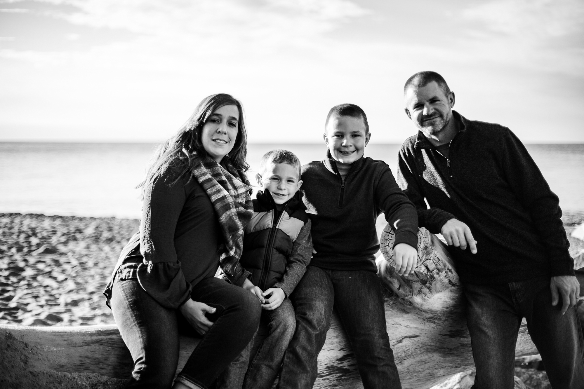 Family sits on large piece of driftwood for Presque Isle family portraits