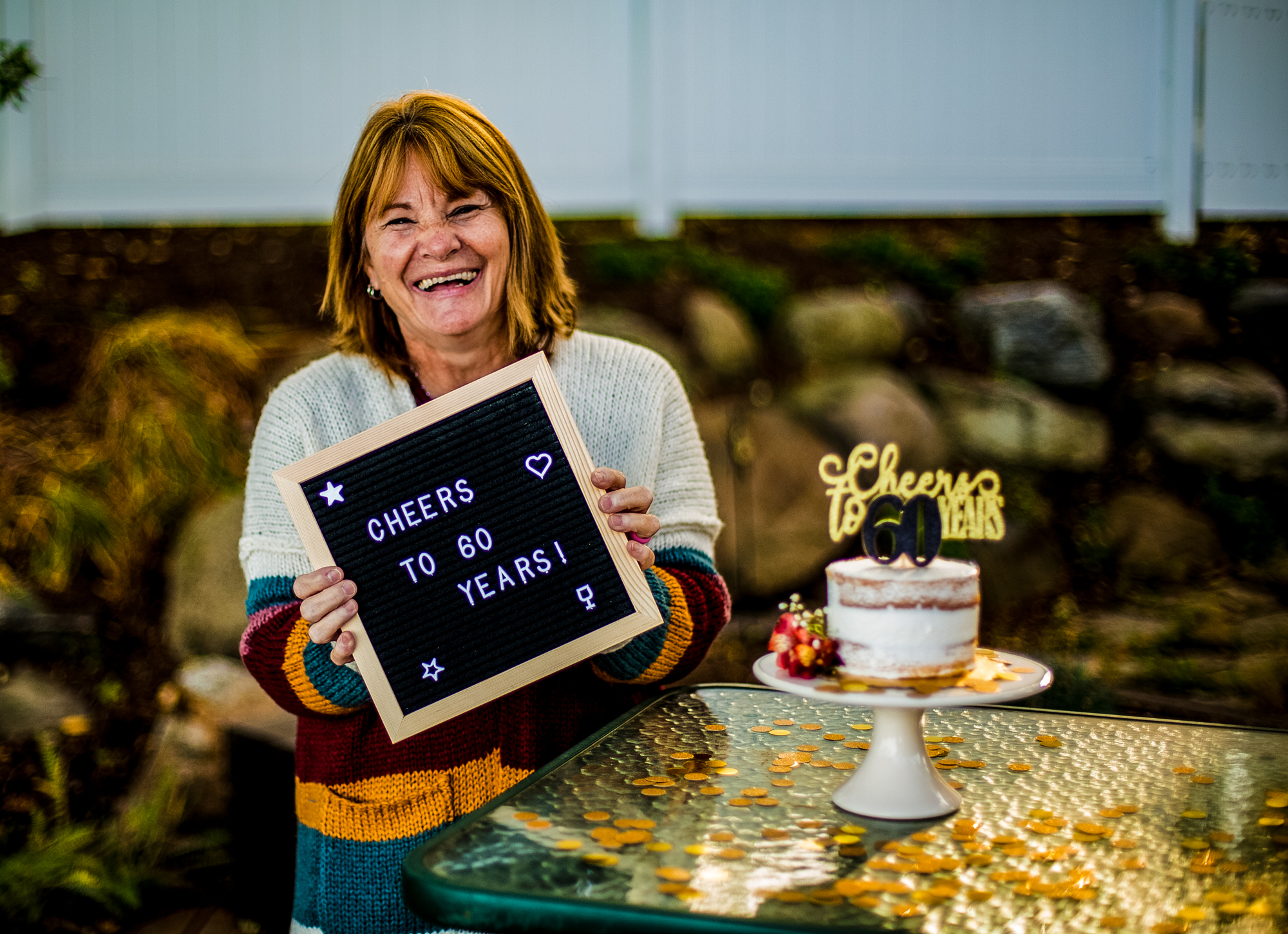 Woman smiles and holds happy birthday sign next to cake for 60th birthday celebration