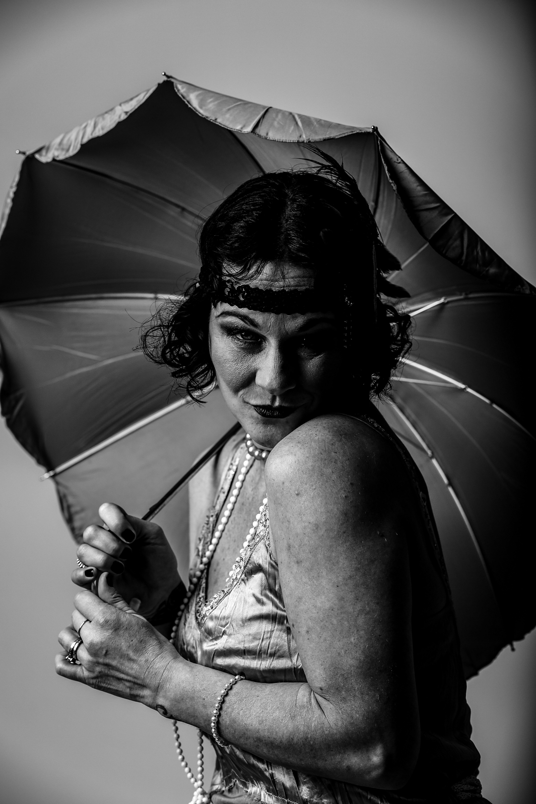 Woman dressed in 1920's fashion poses with umbrella