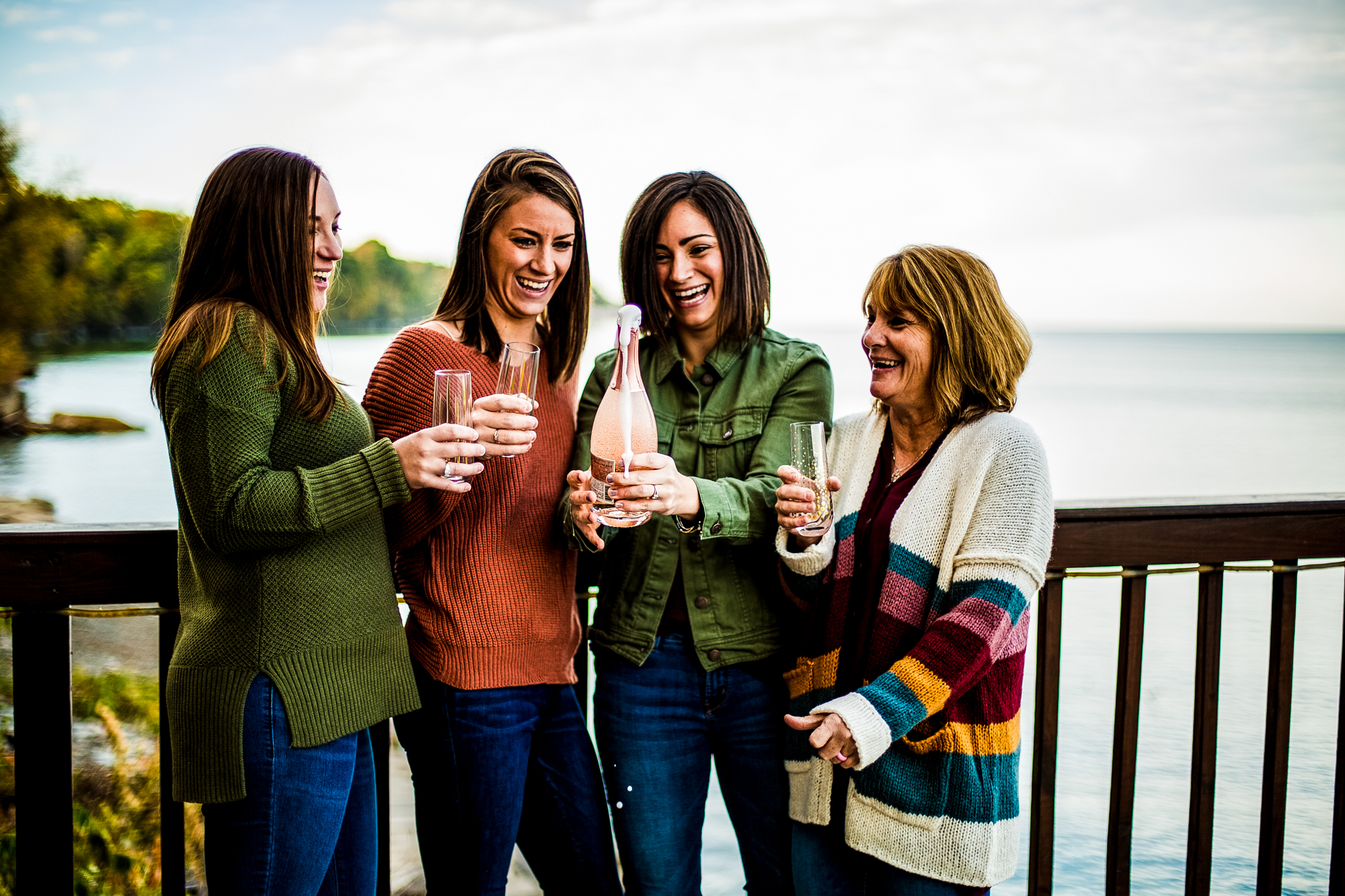 Mother and three daughters laughing as they open a bottle of champagne during family portraits in Erie, PA