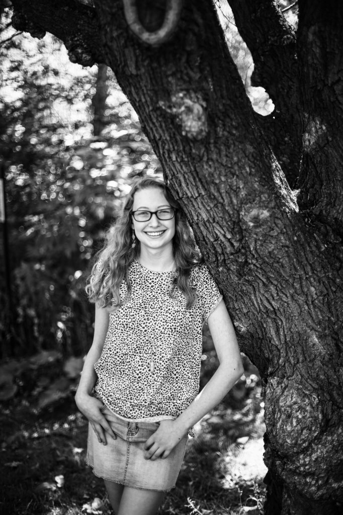 Smiling girl stands next to a tree in Frontier Park for senior photos in Erie PA