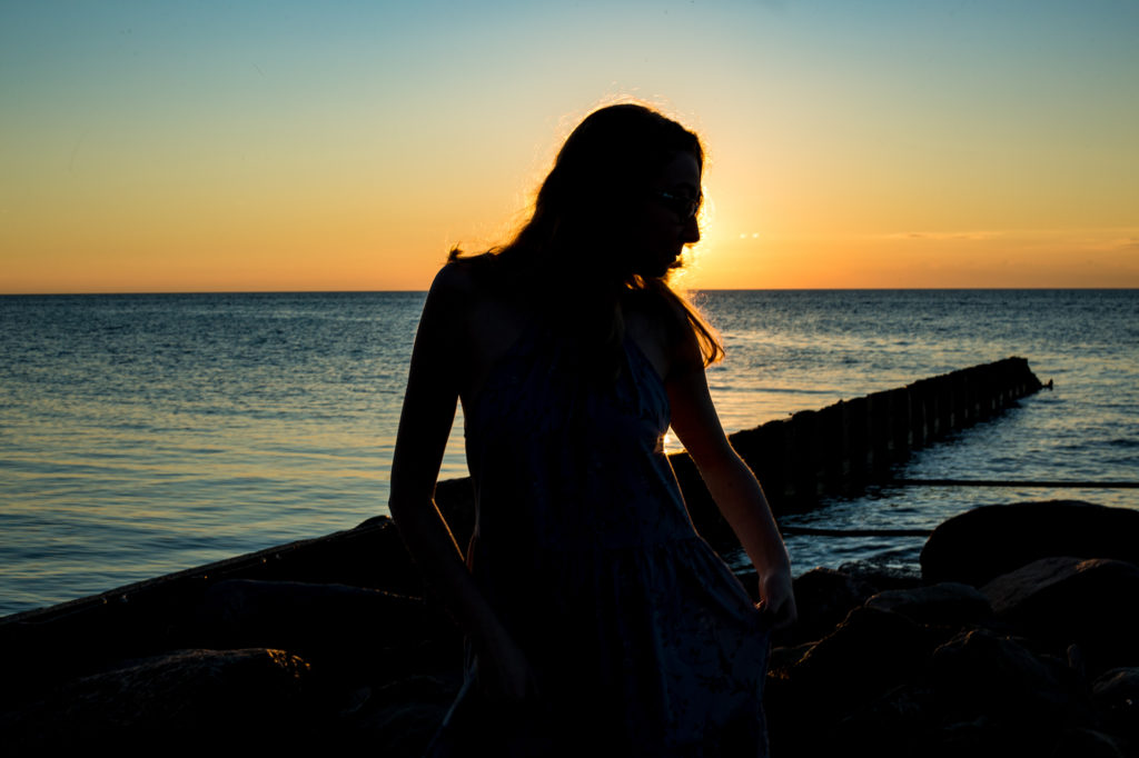 Silhouette of girl on the beach at sunset for senior photos in Erie PA