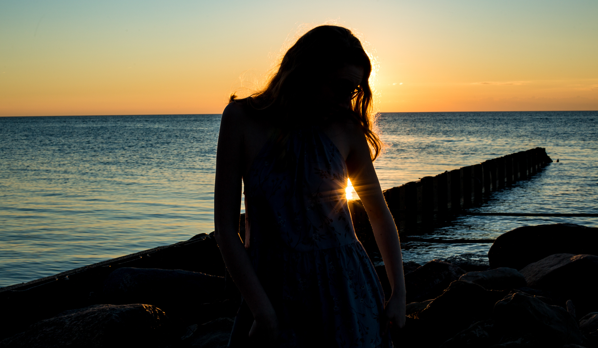 Silhouette of girl at Presque Isle during sunset for senior photos in Erie, PA