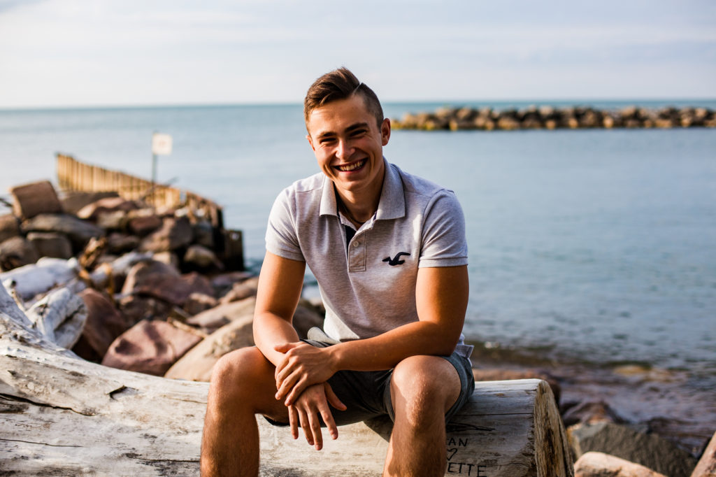 Young man sitting on driftwood and smiling for Lighthouse Beach senior portraits in Erie PAfo