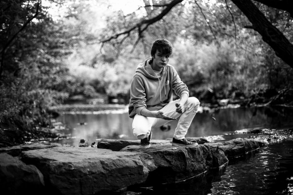 Young man crouches down in Cascade Creek for senior portraits at Frontier Park in Erie, PA
