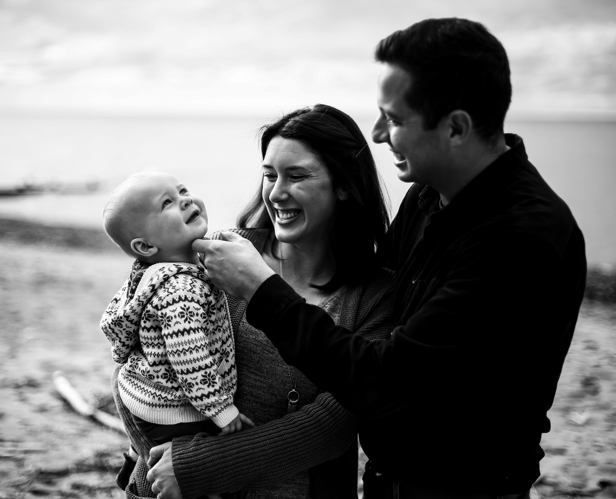 Mother holds baby while father tickles baby's chin in family portrait on Presque Isle State Park in Erie PA