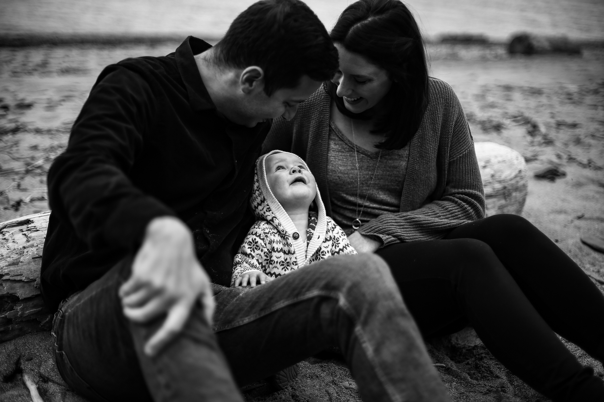 Baby sits between parents and looks up at them for family photos on the beach in Erie, PA