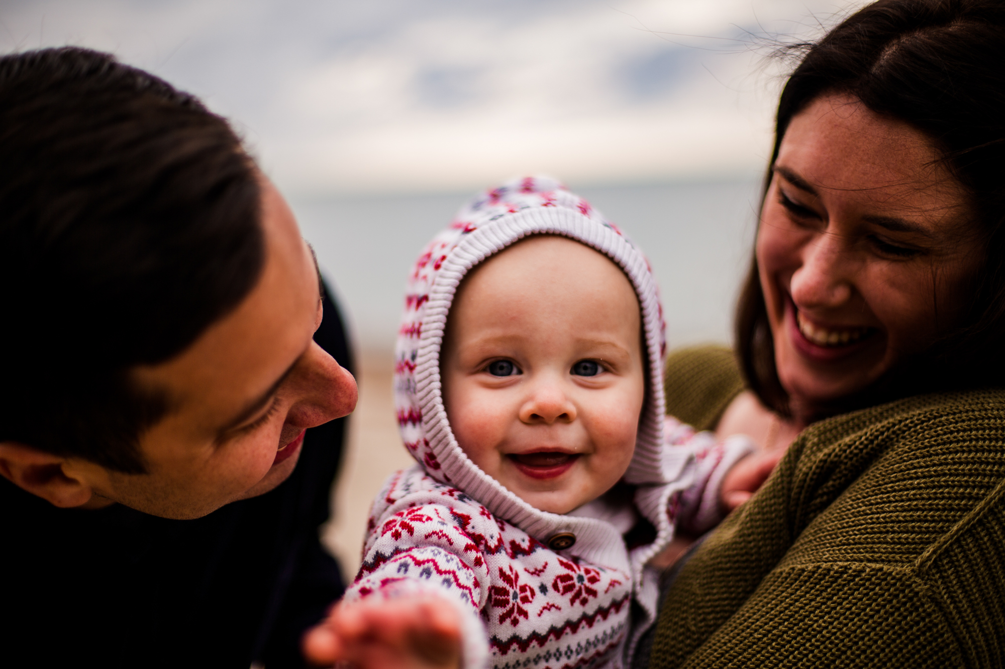 Baby reaches for camera in family portrait with mother and father on Presque Isle in Erie, PA