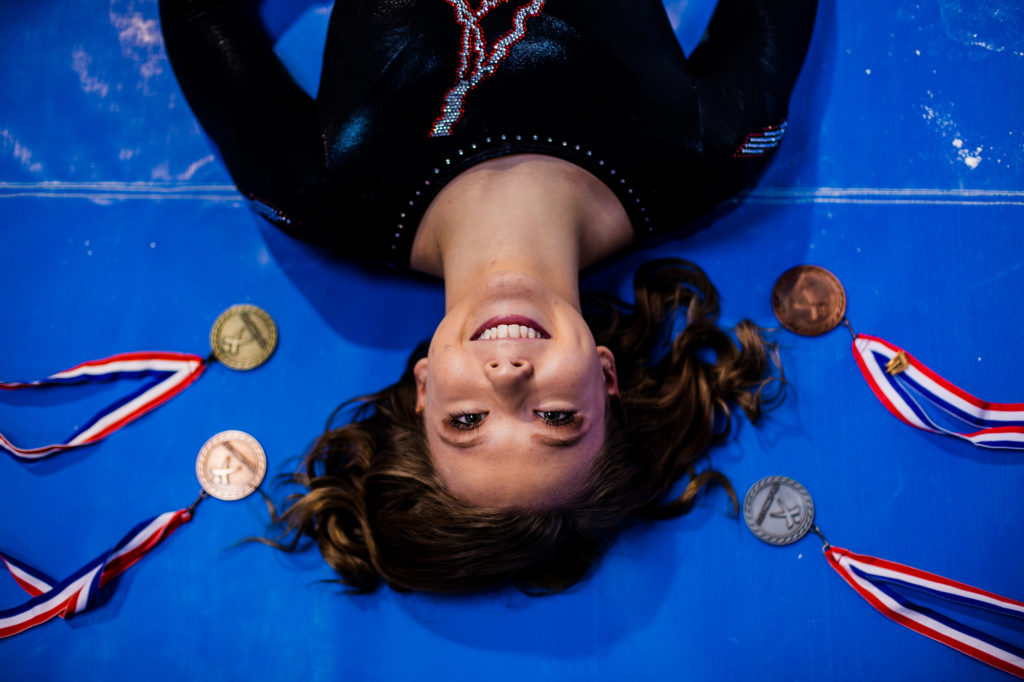 Female gymnast laying on the floor surrounded by her medals