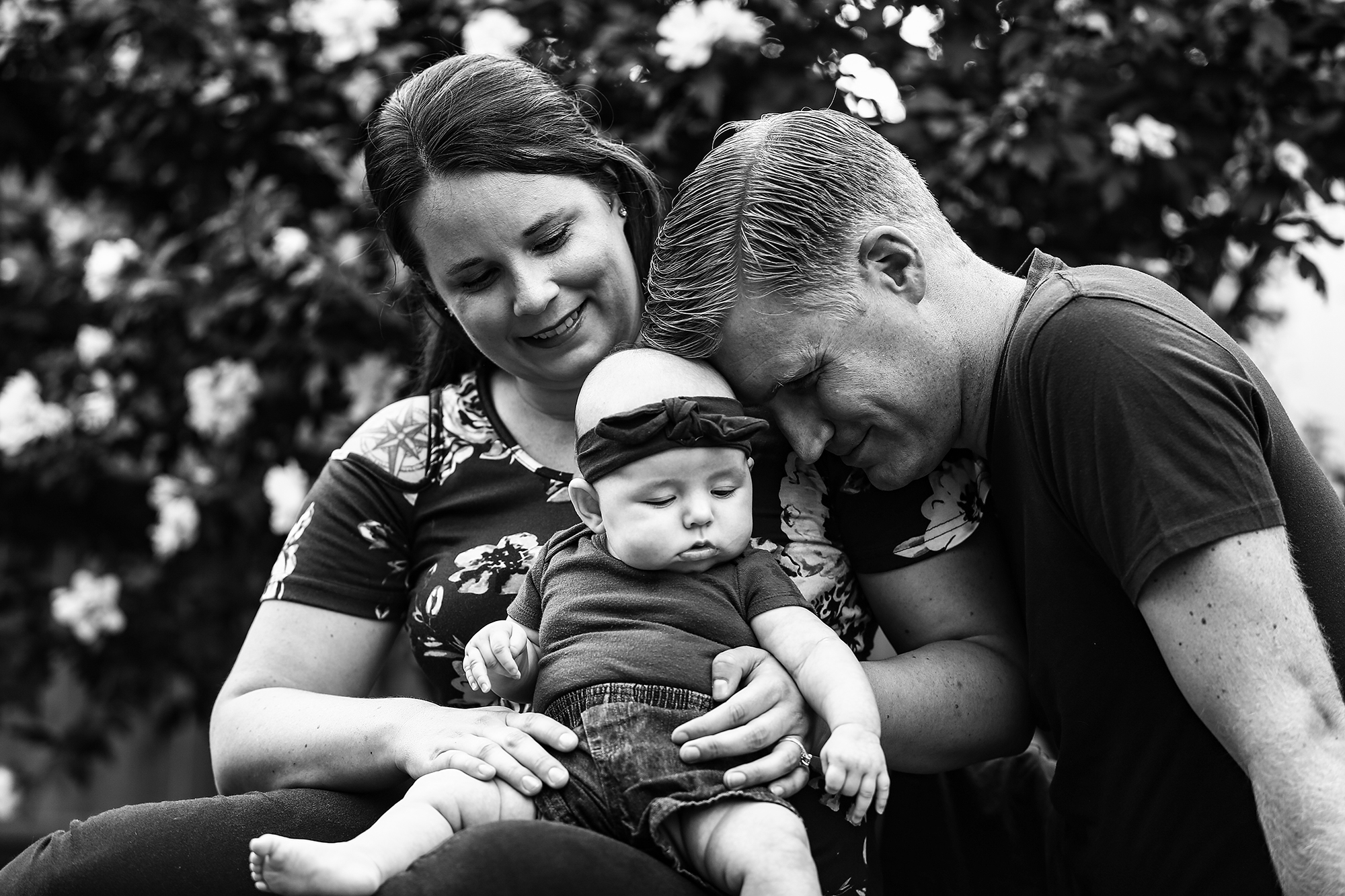 Father rests his forehead on top baby's head while she sits in mother's lap in Erie, PA