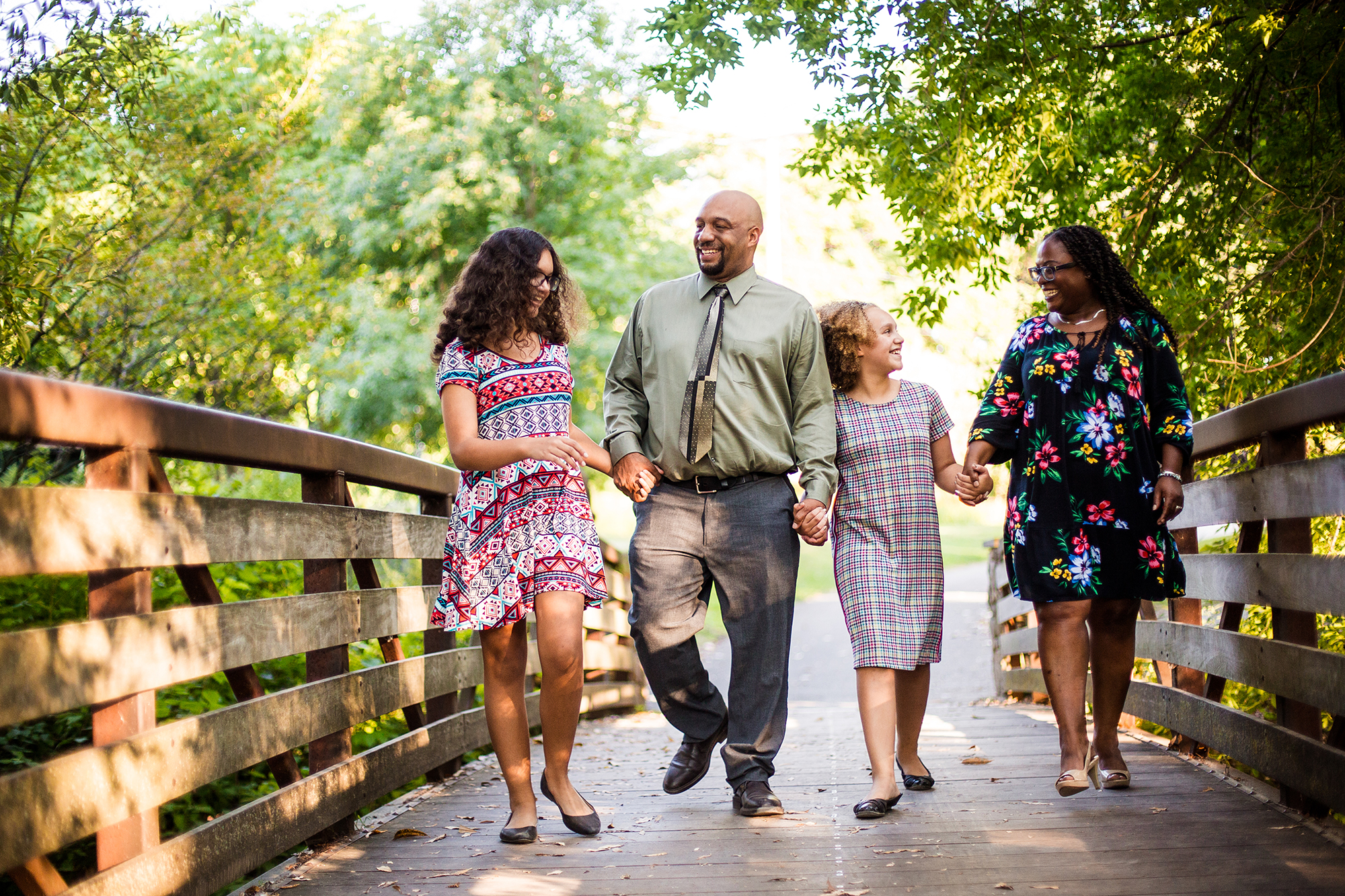 Family of mother, father and two girls walk across the bridge at Frontier Park in Erie PA