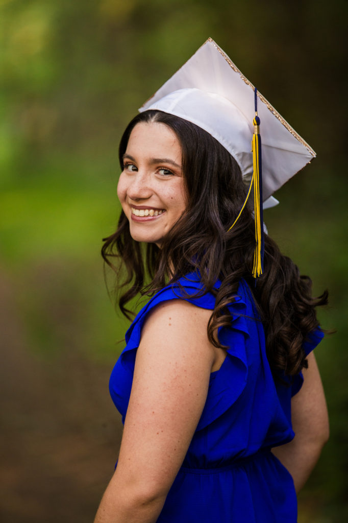 Girl, wearing white graduation cap, looks over her shoulder and smiles