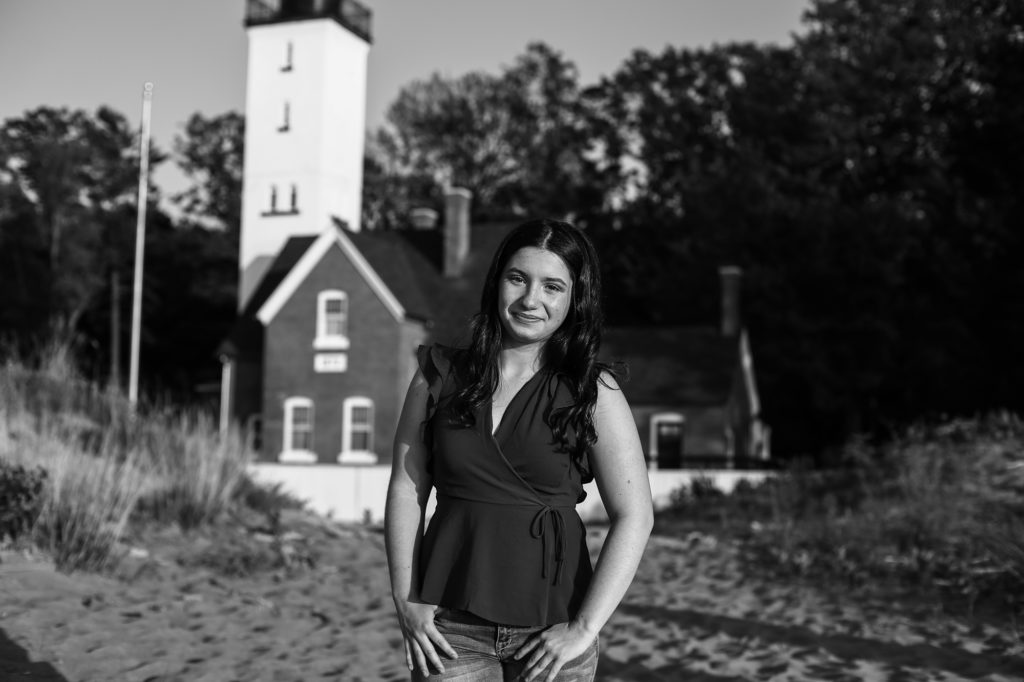 Smiling girl in front of lighthouse for Prseque Isle senior portraits